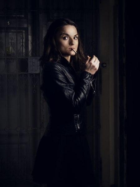 Antigone raucht in der schwarzen Lederjacke.